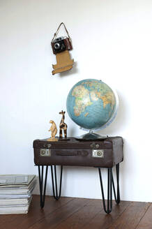 Globe and figurines standing on side table made of old suitcase, with old camera hanging on wall - GISF00479