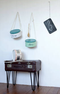 Toy drums made from cookie jars hanging on wall over side table made from an old suitcase - GISF00482