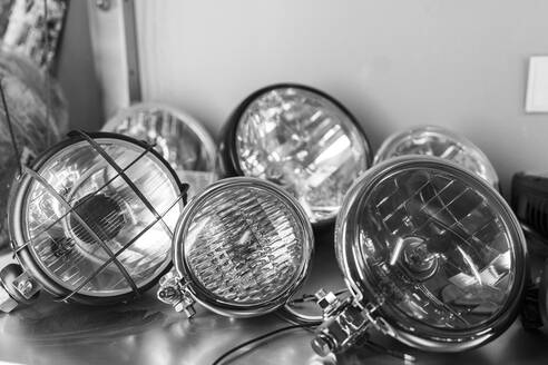 Close-up of various motorcycle headlights lying on shelf - MTBF00245