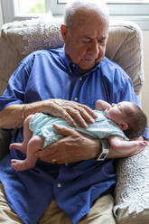 Grandfather sitting in an armchair holding a newborn baby - GEMF03310