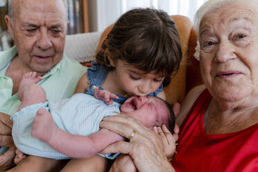 Grandparents with little girl and newborn baby at home - GEMF03313