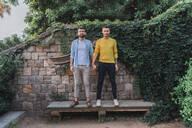 Portrait of gay couple standing hand in hand on stone bench - AFVF04327