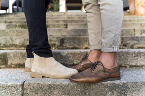 crop view of gay couple wearing leather shoes standing on stairs - AFVF04333