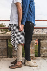 Crop view of gay couple standing back to back holding hands, Barcelona, Spain - AFVF04339