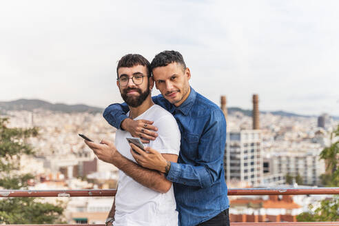 Portrait of happy gay couple with smartphones, Barcelona, Spain - AFVF04342