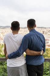 Back view of gay couple looking arm in arm at the city, Barcelona, Spain - AFVF04345