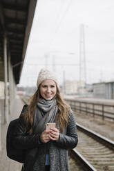 Portrait of smiling young woman with backpack and smartphone standing on platform - AHSF01592
