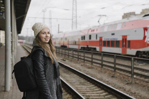 Portrait of smiling young woman with backpack waiting on platform, Vilnius, Lithuania - AHSF01595