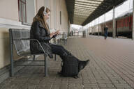 Smiling young woman with backpack sittting on platform using smartphone and headphones, Vilnius, Lithuania - AHSF01598