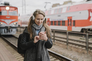 Smiling young woman standing on platform using smartphone and headphones, Vilnius, Lithuania - AHSF01601
