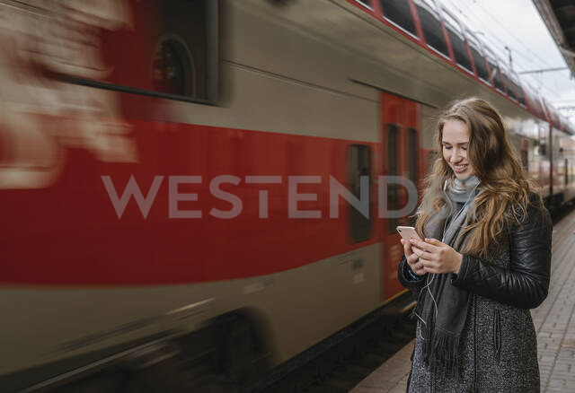 Smiling young woman standing on platform using smartphone and earphones, Vilnius, Lithuania - AHSF01604 - Hernandez and Sorokina/Westend61