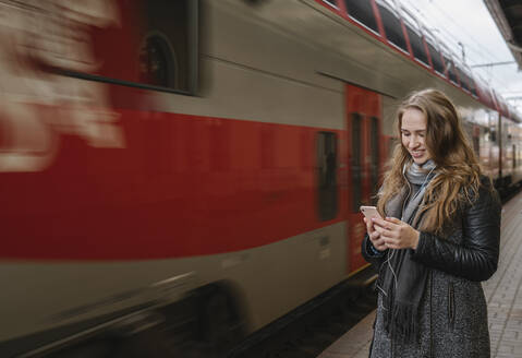 Smiling young woman standing on platform using smartphone and earphones, Vilnius, Lithuania - AHSF01604