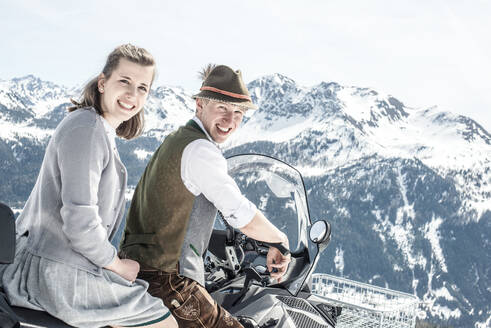 Happy couple in the snowy mountains sktting on snowmobile, Salzburg State, Austria - HHF05587