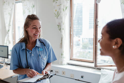 Smiling female nurse talking with patient in hospital - MASF14828