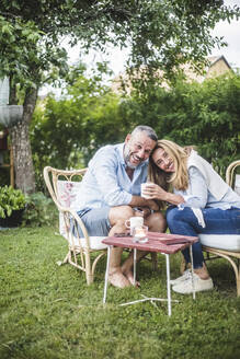 Portrait of loving happy mature couple having coffee in backyard - MASF14930