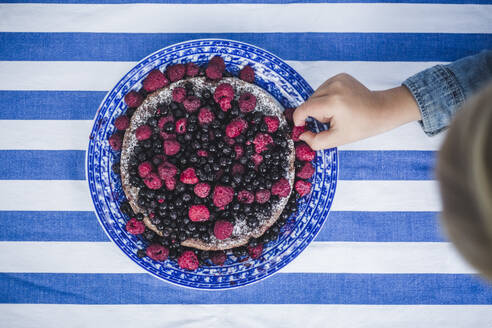 Directly above shot of boy picking up raspberry in tart at table - MASF14945