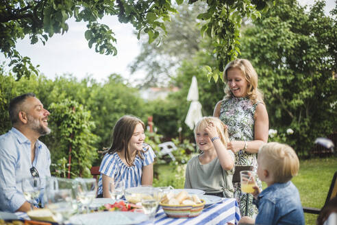 Family having fun at dining table in garden party during summer weekend - MASF14987