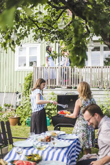 Daughter and mother preparing barbecue food while smiling man sitting at table in backyard during weekend - MASF14996