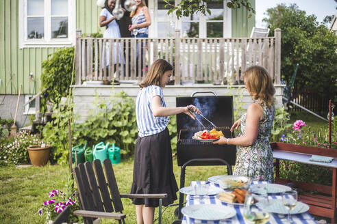Mother and daughter preparing food on barbecue in backyard party - MASF15002