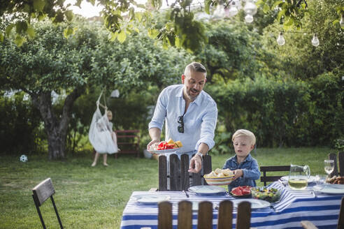 Mature father directing son with food plate while pointing at table in yard - MASF15014