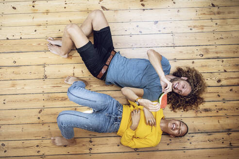 Happy young couple lying on the floor at home sharing a watermelon - MCF00529