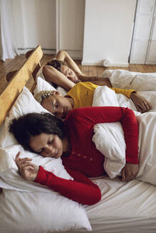 Three friends sleeping in bed at home - MCF00532