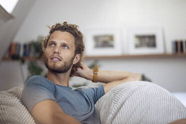 Young man relaxing in beanbag at home - MCF00538