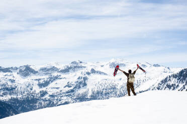 Man with backpack, standing on mountain summit, waving with his snowshoes, rear view, Salzburg State, Austria - HHF05591