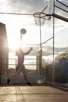 Teenager playing basketball, dunking against the sun - CJMF00189