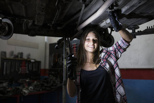 Casual woman with lamp standing under car bottom on leveling system and smiling at camera working in service - ABZF02866