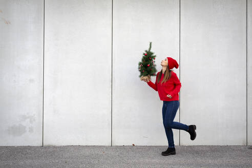 Woman wearing red pullover and wolly hat, holding artificial Christmas tree in front of a wall - HMEF00685