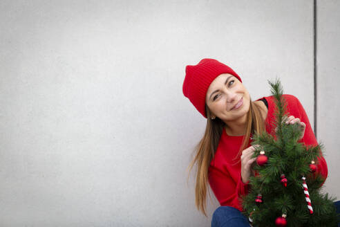 Woman wearing red pullover and wolly hat, holding artificial Christmas tree in front of a wall - HMEF00688