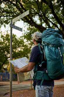 Backpacker checking the name of a street in his map - VEGF01011