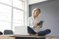 Smiling young businesswoman sitting on desk in office using tablet - MOEF02642