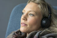 Portrait of young woman listening to music with headphones - MOEF02645