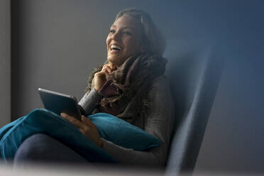 Laughing young woman sitting in armchair using tablet - MOEF02648