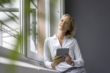 Young businesswoman holding tablet at the window - MOEF02651