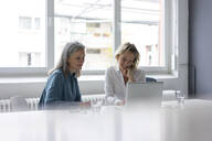 Two businesswomen using laptop at desk in office together - MOEF02669