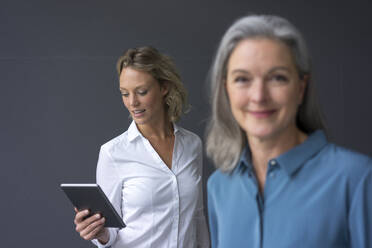 Young businesswoman using tablet with mature businesswoman in foreground - MOEF02678