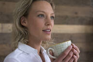 Young businesswoman holding cup of coffee looking sideways - MOEF02681