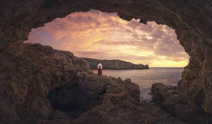 Rear view of man sitting on cave at sunset, Menorca, Spain - DVGF00070