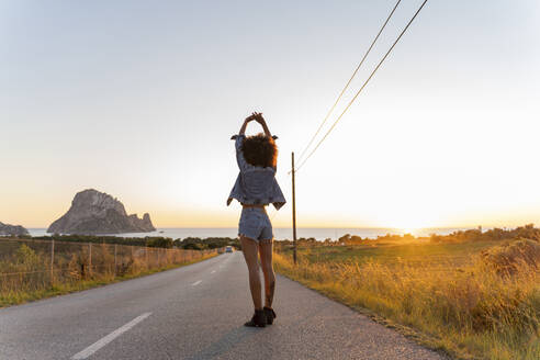 Young woman standing on street with raised arms at sunset, Ibiza - AFVF04366