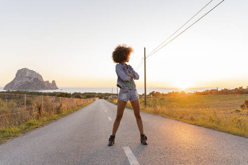 Young woman standing on street and watching the sunset, Ibiza - AFVF04369