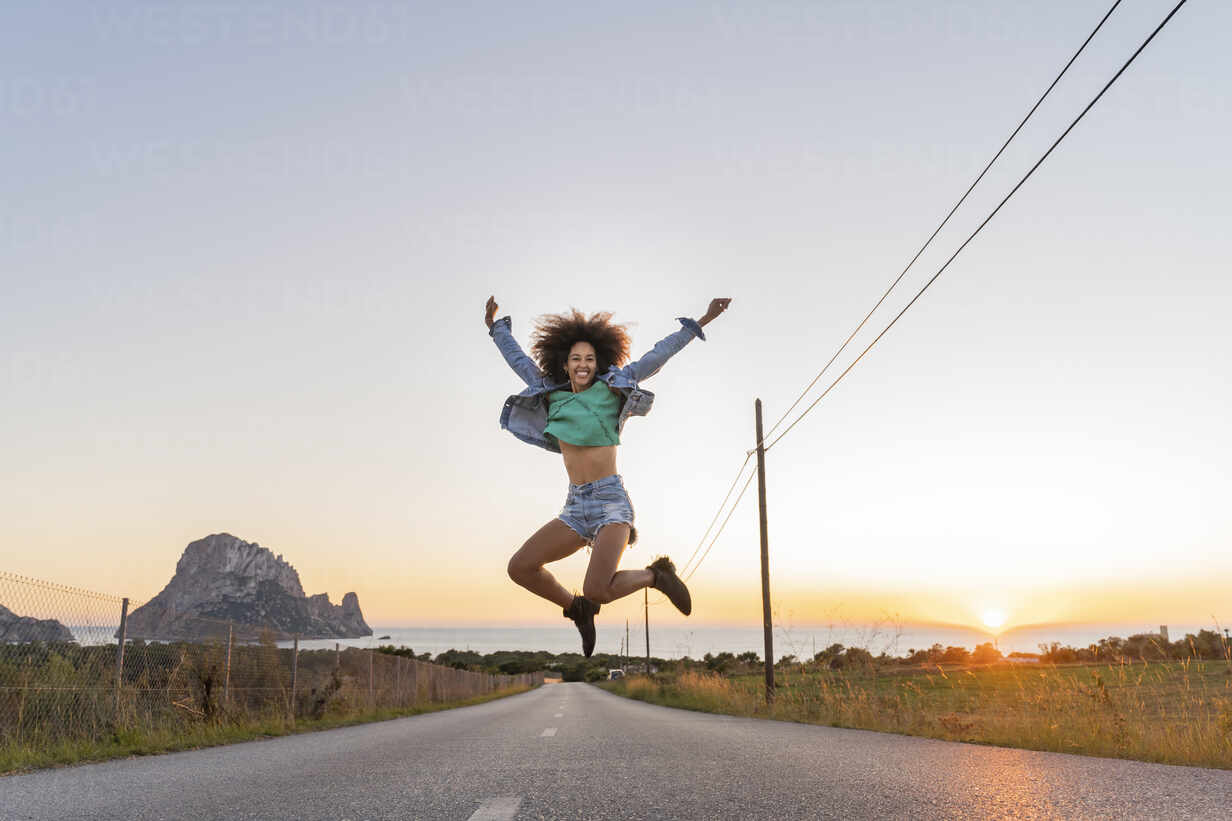 Young woman jumping on street at sunset, Ibiza - AFVF04372 - VITTA GALLERY/Westend61