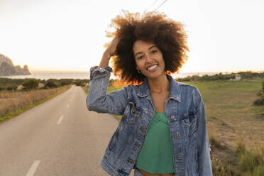 Young woman standing on street at sunset, hand in hair - AFVF04375