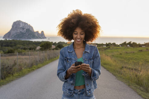 Young woman on a road using smartphone, Ibiza - AFVF04378