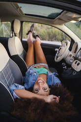 Young woman during road trip, layng in car - AFVF04384
