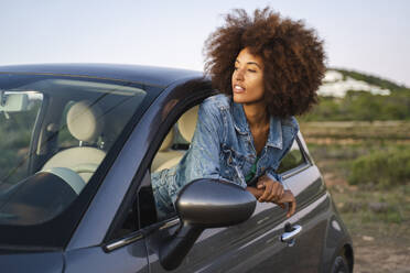 Young woman during road trip, leaning out of window - AFVF04387