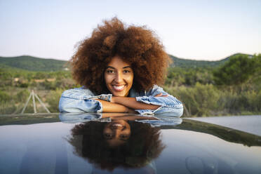 Young woman during road trip, leaning on car roof and looking at camera - AFVF04390