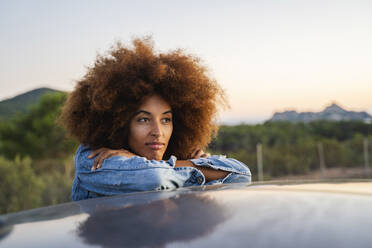 Young woman during road trip, leaning on car roof - AFVF04393
